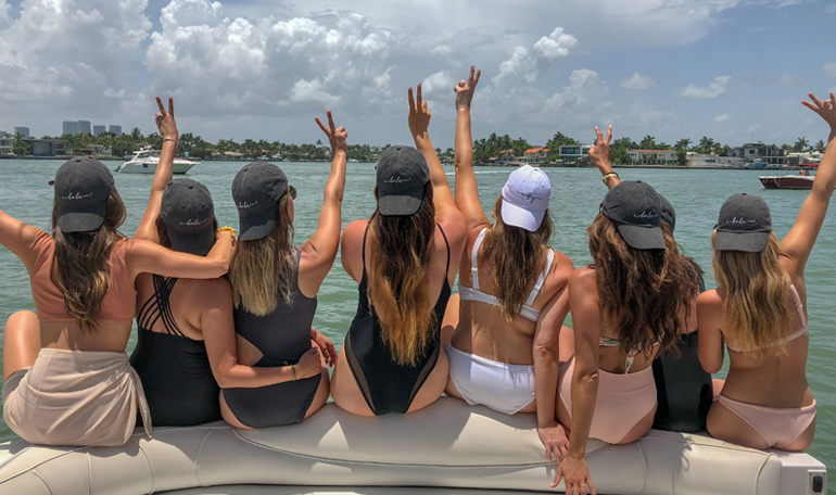 A group of girls pose for a photo on the bow of the yacht for their bachelorette charter.