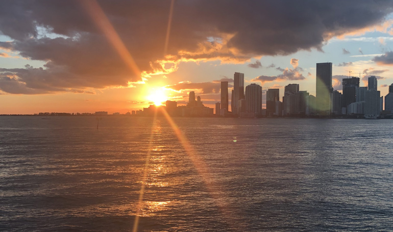 The sun sets behind the Miami skyline viewed from the Black Ice yacht.